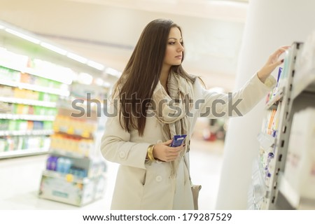 Young woman buying personal care products - stock photo