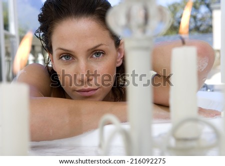 Young woman by candles, portrait, close-up - stock photo