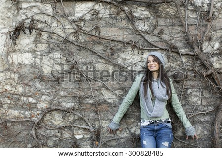 Young woman by the wall at autumn