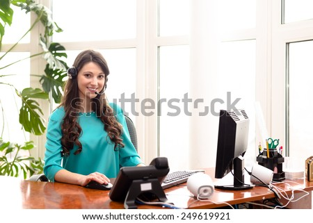 Young woman call centre operator speaking on headphones at work place with computer - stock photo