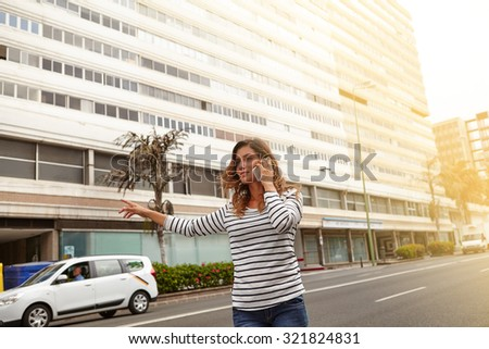 Young woman calling a taxi on city avenue while talking on mobile phone
