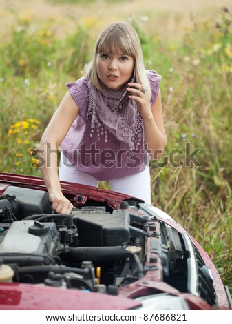 Young  woman calling by mobile to auto support - stock photo