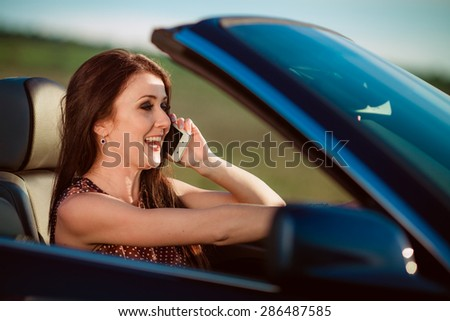 Young woman calling by phone while driving car - stock photo