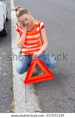 Young woman calling with her mobile phone beside her broken down car - stock photo