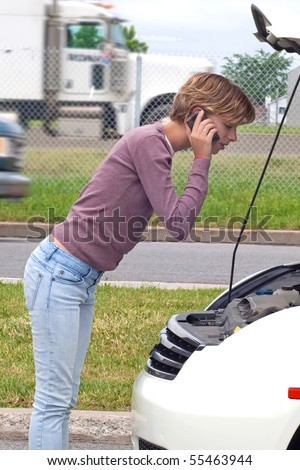 young woman calls for assistance for breakdown along busy highway - stock photo