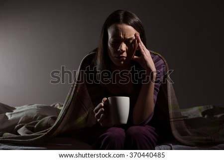 Young woman can not sleep. She is sitting on her bed and drinking tea. - stock photo