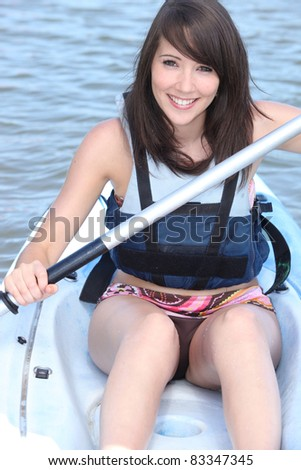 young woman canoeing - stock photo