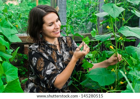 young woman caring for cucumbers in garden