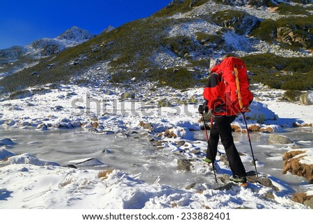 Young woman carries a backpack across frozen river on the mountains - stock photo