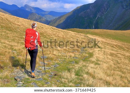 Young woman carries red backpack on green mountain trail  - stock photo
