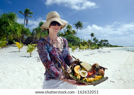 Young woman carry a tropical food of grilled fish, fruits and vegetables dish served on deserted tropical island in Aitutaki lagoon, Cook Islands. - stock photo