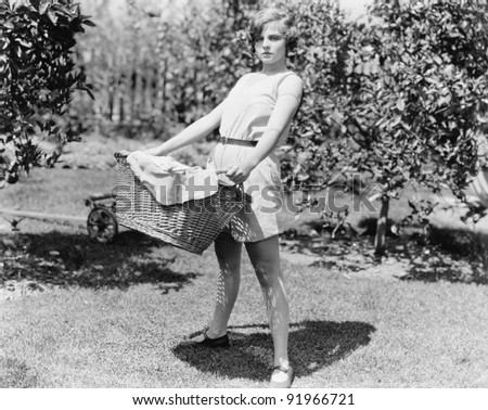 Young woman carrying a basket of laundry