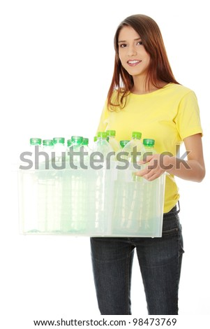 Young woman carrying a plastic container full with empty recyclable plastic. Recycling concept - stock photo
