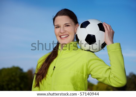 Young woman carrying a soccer ball on her shoulder