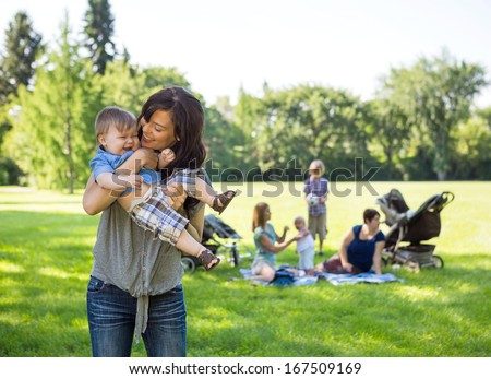 Young woman carrying baby boy with friends and children in background at park - stock photo