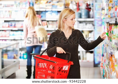 Young woman carrying basket while shopping in the supermarket - stock photo