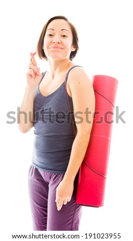 Young woman carrying exercise mat wishing with crossing fingers - stock photo