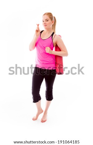 Young woman carrying exercising mat wishing with crossing fingers - stock photo