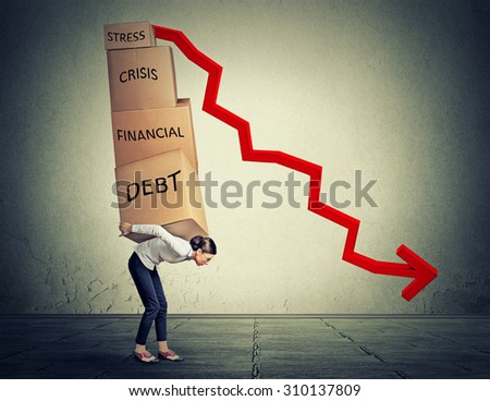 Young woman carrying heavy boxes full of financial debt walking along gray wall background  - stock photo