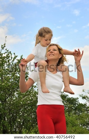 Young woman carrying her daughter over the shoulders