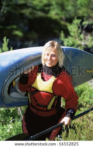 Young woman carrying kayak - stock photo