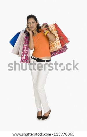 Young woman carrying shopping bags and looking afraid
