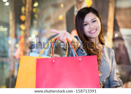 young woman carrying shopping bags and smiling in mall