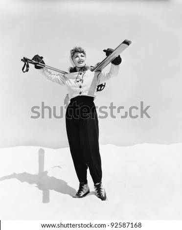Young woman carrying ski and ski pole on her shoulders - stock photo