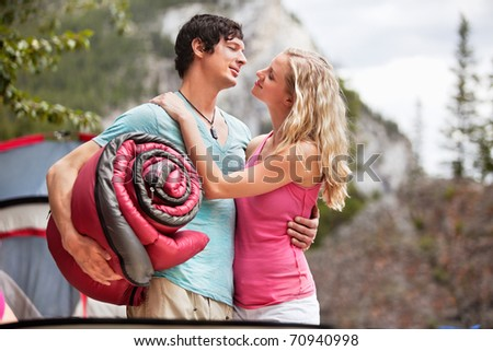 Young woman carrying sleeping bag and embracing woman while camping - stock photo