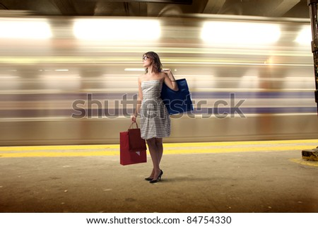 Young woman carrying some shopping bags in an underground station