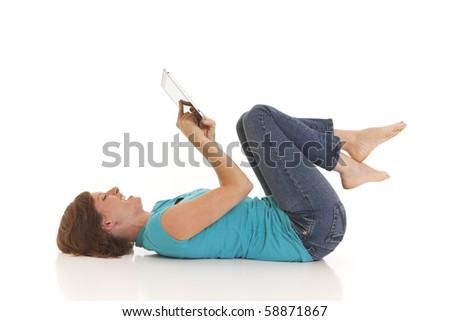 Young woman casually laying on floor with a tablet computer - stock photo