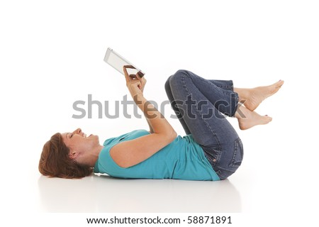 Young woman casually laying on floor with a touchscreen - stock photo