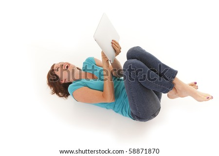 Young woman casually laying on floor with a touchscreen computer - stock photo