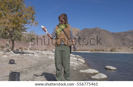 Young woman catching grayling in the river in Mongolia
