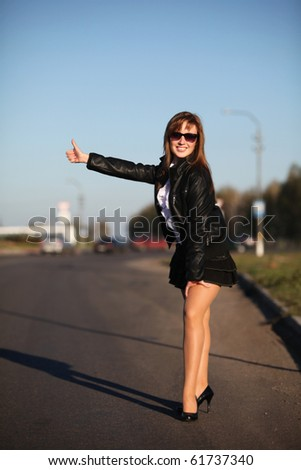 Young woman catching taxi on the road - stock photo