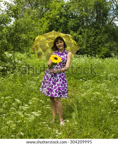 Young woman, Caucasian, brunette, standing with sunflower and yellow umbrella in park, summer. - stock photo