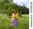 Young woman, Caucasian, brunette, with sunflower on a meadow in blossom in park. - stock photo