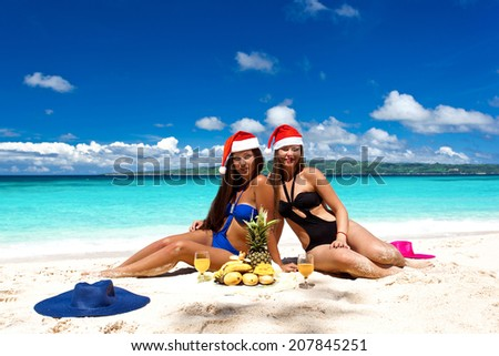 Young woman celebrating Christmas, having exotic picnic with fruits