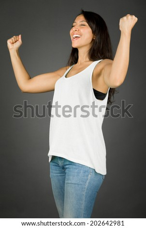 Young woman celebrating her success with fist up and smiling - stock photo