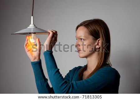 young woman changing a light bulb - stock photo