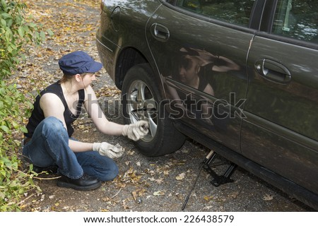 Young woman changing a tire crouching down at the side of the car - stock photo