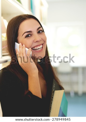 Young woman chatting on a smart phone glancing across at the camera with a happy beaming smile as she holds a large text book in her hands - stock photo
