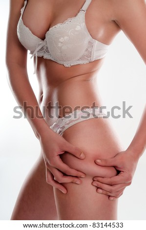 Young woman checking cellulite and folding skin on hip