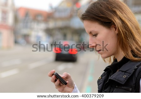 Young woman checking for text messages on her mobile phone as she waits a to cross the street at a red pedestrian crossing - stock photo