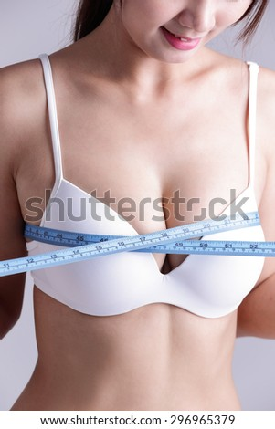 young woman checking her breast measurement isolated over gray background, asian beauty