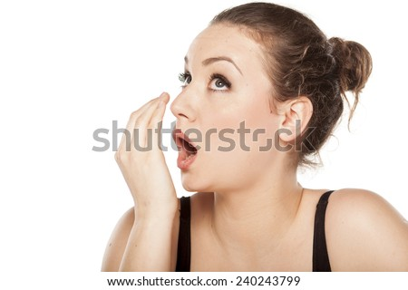 young woman checking her breath with her hand - stock photo