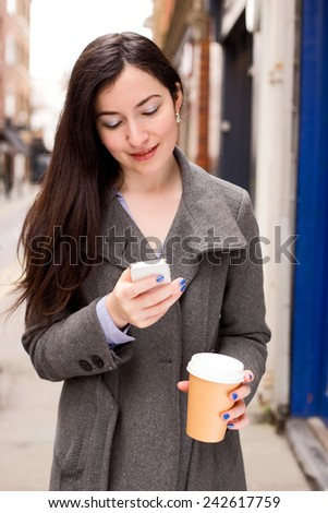 young woman checking her text messages with a coffee - stock photo
