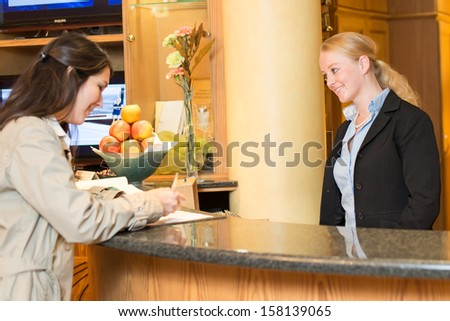 Young woman checking in at the hotel reception with friendly receptionist - stock photo