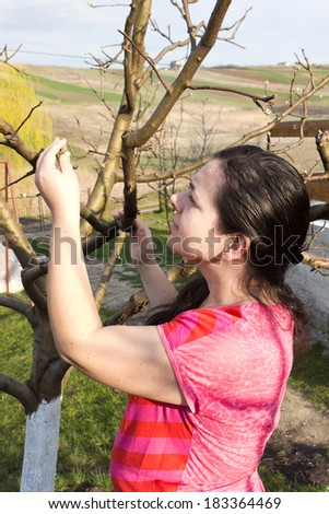 Young woman checking tree branches