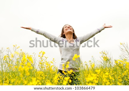 Young woman cheering in the field - stock photo